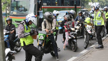 Motorcyclists, police and pedestrians share roads and footpaths in Jakarta, Indonesia