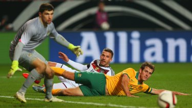Socceroos Mat Ryan and Luke DeVere watch a cross go past as Germany's Lukas Podolski slides in the background.