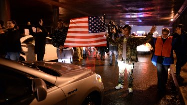 Demonstrators block an intersection during a march to protest the death of Michael Brown.