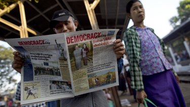 A man reads a newspaper featuring Myanmar's opposition leader Aung San Suu Kyi's meetings with President Thein Sein and General Min Aung Hlaing.