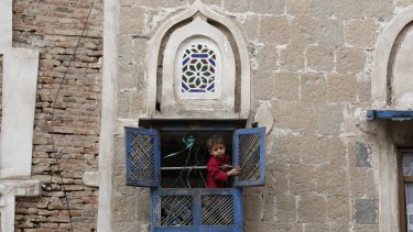 A boy looks out from the window of his house in the Old City in Sanaa, Yemen, earlier this month.