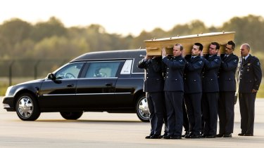 Dutch military men carry a coffin containing the remains of a victim of flight MH17.