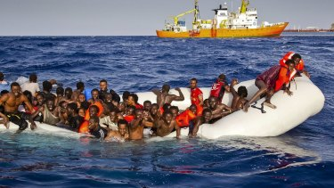 Migrants ask for help from a dinghy in the Mediterranean.