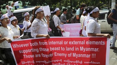 Protesters in Myanmar hold a placard describing migrants in the Bay of Bengal as beasts.