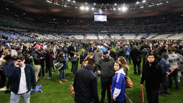 Terrified: Spectators gather on the pitch at Stade de France after news of the bombing and terrorist attacks reached the fans.