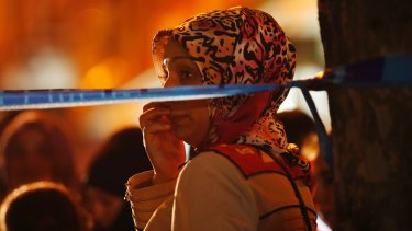 A woman watches behind a police line at the scene of a blast in Istanbul on Thursday.