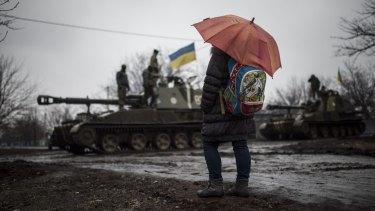 A schoolgirl watches Ukrainian armoured vehicles on the outskirts of Donetsk, in Ukraine, on Wednesday.