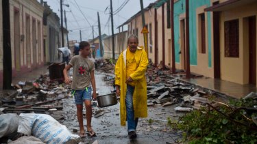 Residents carry food down a street strewn with rubble caused by Hurricane Matthew in Baracoa, Cuba.