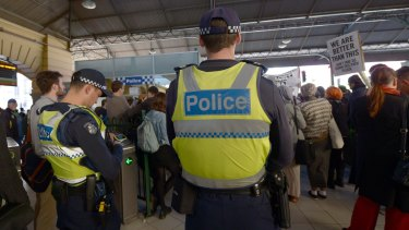 Police watch as protesters rally inside Flinders Street Station on Friday against    Australian Border Force officers taking part in Operation Fortitude.