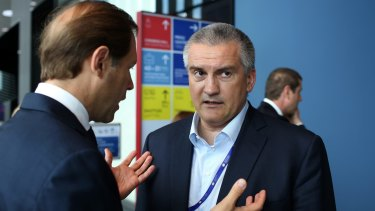 """Sergey Aksyonov, """"prime minister"""" of the autonomous republic of Crimea, right, attends the opening day of the St Petersburg International Economic Forum   in June."""