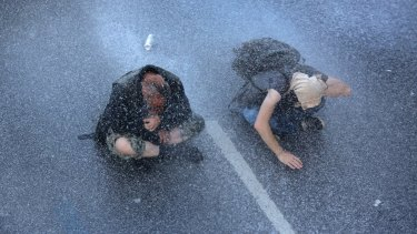 Two protesters sit on a street while the police use a water canon in Hamburg, northern Germany, on Thursday.
