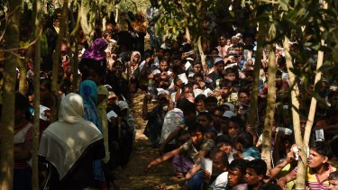 Rohingya refugees line up at a Red Cross distribution point in Burma Para refugee camp, Cox Bazaar, Bangladesh.