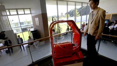 A porter robot escorts a guest while carrying his suitcase at the new hotel, in Sasebo, southwestern Japan.