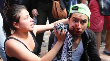 A woman aids a man injured during clashes between animal rights activists and police ahead of the January bullfight.