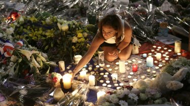 A woman lights candles at a memorial for the victims of the Bastille Day attack in Nice.