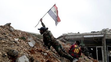 A Syrian army soldier places a Syrian national flag during a battle with rebel fighters at the Ramouseh front line, east of Aleppo.
