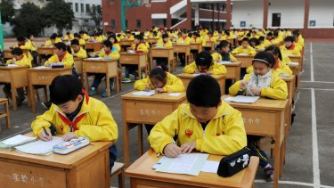 Chinese primary school students compete in calligraphy on the playground in Dongyang of Jinhua City.