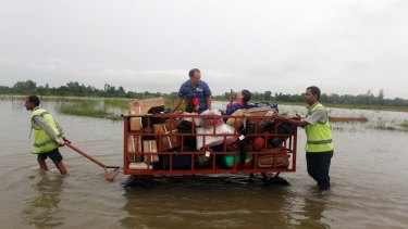 Passengers find their space in a luggage trolley as airport staff maneuver it through Nepal's flooded Janakpur airport in August.