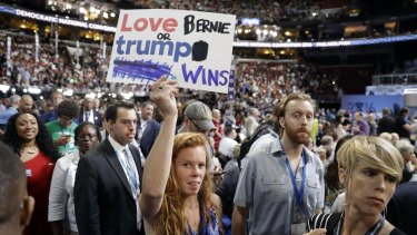"""A """"love trumps hate"""" sign issued by the Hillary Clinton campaign is modified by a Sanders supporter on the convention floor."""