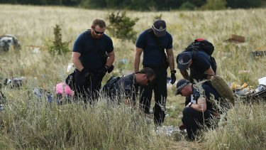 Australian Federal Police officers and their Dutch counterparts collect human remains from the MH17 crash site in the fields outside the village of Grabovka in eastern Ukraine in August of last year.