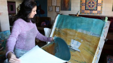 Palestinian artist Maha al-Daya, 39, with some of her unfinished work that captures the fishing boats of Gaza.