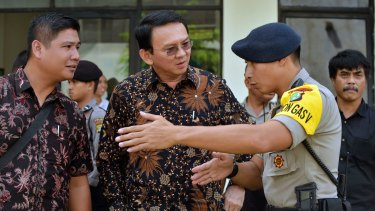 Jakarta governor Basuki Tjahaja Purnama, popularly known as Ahok, centre, listens to a police officer explain the plan for leaving North Jakarta District Court.