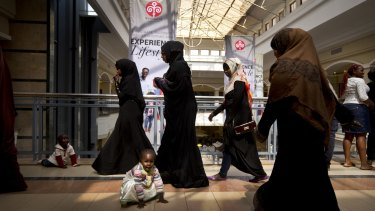A young Kenyan girl and her brother play on the floor while other shoppers walk around the reopened Westgate Shopping Mall.