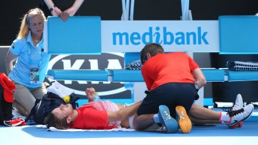 Oliver Anderson receives medical attention during last year's Australia Open, where he claimed the boys' title.