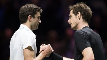 Gilles Simon (left) and Andy Murray shake hands at the end of their match in Rotterdam.