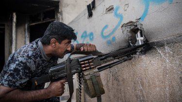 An Iraqi policeman fires a machine gun at an Islamic State position during the battle to recapture west Mosul.