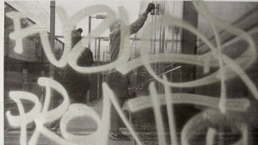 A tagger tags the exhibition of grafitti.