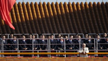 Security officers sit on the Tiananmen Gate, ahead of the military parade.