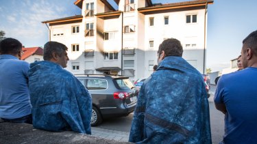 Residents sit in front of an accommodation for asylum seekers in Heppenheim, Germany.
