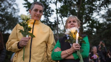 Prayers for condemned pari: A couple holds candle and flowers as part of an Amnesty international vigil for the Bali 9 duo.