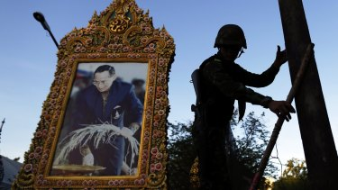 A soldier in front of a picture of Thailand's King Bhumibol Adulyadej amid anti-government protests in central Bangkok in May.