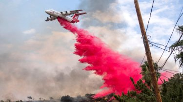 A plane makes a drop on a hillside in Sun Valley neighborhood, north of Los Angeles on Saturday