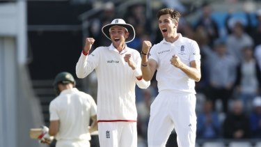 England's Steven Finn and Stuart Broad celebrate the wicket of Mitchell Johnson.