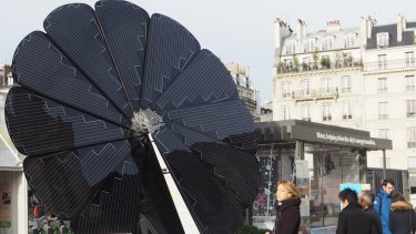 Parisians take in the renewable energy offerings of the future, including this solar 'smartflower' that opens as the sun rises and follows it through the day.