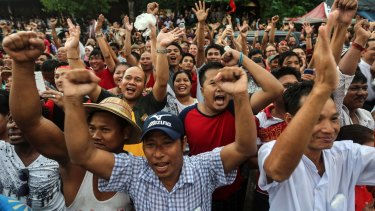 National League for Democracy party supporters cheer as they gather to hear first election results outside the party headquarters, in Yangon, on Sunday.