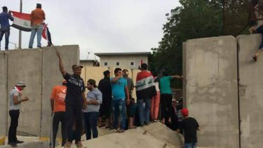 Supporters of Shiite cleric Muqtada al-Sadr storm the blast walls surrounding Baghdad's highly fortified Green Zone.