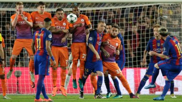 City's defensive wall tries to block a Messi free kick.