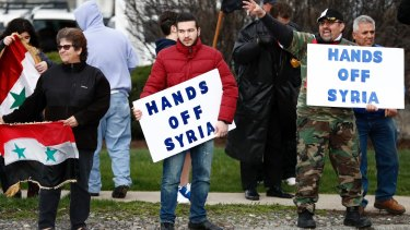 People hold signs during a rally in opposition to the US airstrikes in Syria in Allentown, Pennsylvania. Allentown has one of the US's largest Syrian populations, mostly Christian and in support of Syrian President Bashar al-Assad.