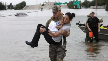 Houston Police SWAT officer Daryl Hudeck carries Connie Pham and her 13-month-old son Aiden after rescuing them from their home.