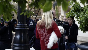 A resident holds her dog while talking to reporters at an upscale apartment complex in Irvine, California after a raid.