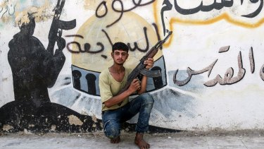 A Free Syrian Army fighter poses   in front of a mural left by Islamic State militants in Jarablus after its liberation.
