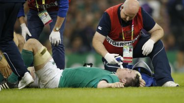 Ireland's Peter O'Mahony receives treatment for a knee ligament injury during the final pool game against France.