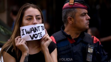 A pro-independence demonstrator cover her mouth with a banner next to a Catalan police officer in Barcelona, Spain.