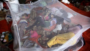 Ethnic Rohingya women and children sleep under mosquito net at a temporary shelter in Langsa, Aceh province.