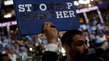 """A delegate holds a sign altered to read """"Stop Her"""" during the Democratic convention in Philadelphia."""