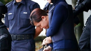 Indonesian suspect Siti Aisyah, centre, is escorted by police officers in Sepang, Malaysia, on Thursday.